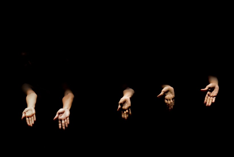 Dancers' hands are illuminated during a performance by the National Ballet of Panama at the National Theater in Panama City, Wednesday, May 9, 2012. (AP Photo/Arnulfo Franco)